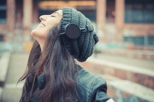 jovem bela mulher morena ouvindo música com fones de ouvido na cidade