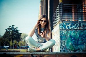young beautiful brunette woman listening to music in the city