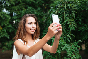 Young beautiful brunette woman making selfie with smartphone outdoors with green leaves on background