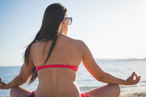 young beautiful brunette woman making yoga at the beach in summertime
