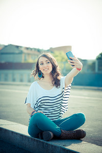 young beautiful brunette woman selfie with smart phone in the city
