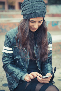 young beautiful brunette woman using smartphone in the city