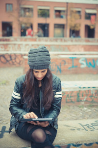 young beautiful brunette woman using tablet in the city