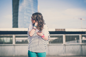 young beautiful brunette woman with smart phone in the city