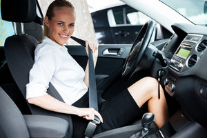 Young beautiful business woman fastens her seat belt while sitting in car