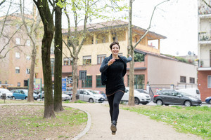 Young beautiful cacuasian woman running free smiling outdoor in the city - freedom, carefree, power concept