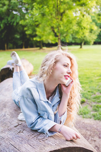 Young beautiful caucaisan long blonde curly hair woman lying on a trunk in a city park, talking smart phone - communication, technology, gossip concept