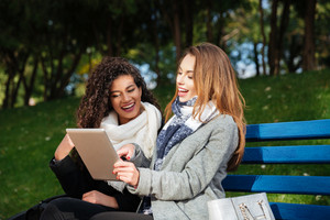 Young beautiful caucasian and african ladies wearing scarfs sitting on a bench outdoors. Looking at tablet and pointing on it.