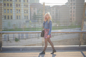 Young beautiful caucasian blonde girl walking through streets talking smartphone - technology, communications, social network concept - wearing jeans shirt and floral skirt - overlooking right