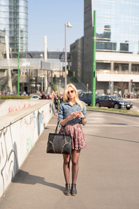 Young beautiful caucasian blonde girl walking through the streets of the city using a smartphone - technology, communications, social network concept - wearing jeans shirt and floral skirt