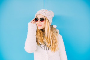 young beautiful caucasian blonde hair woman leaning on a blue wall, wearing sunglasses overlooking, smiling - happiness, confident, having fun concept