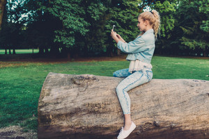 Young beautiful caucasian blonde hair woman outdoor in city park lying on a trunk using smart phone taking selfie - technology, social network, communication concept