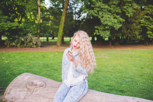 Young beautiful caucasian blonde hair woman outdoor in city park lying on a trunk using smart phone - technology, social network, communication concept