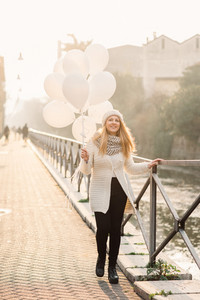 young beautiful caucasian blonde hair woman outdor in the city holding white balloon - happiness, celebration, party concept