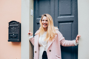 young beautiful caucasian blonde hair woman standing on the front door, overlooking smiling - happiness, having fun, smiling concept
