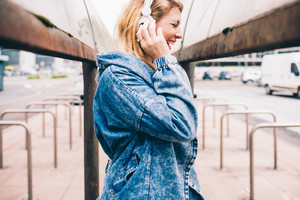 Young beautiful caucasian blonde woman listening music with headphones smiling outdoor in the city - happiness, relaxing, music concept