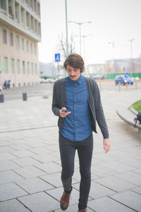 young beautiful caucasian brown hair man with moustache using a smartphone - technology, social network, communication, business concept