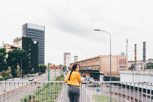 Young beautiful caucasian brown hair woman leaning on handrail with city in background, turning looking in camera, smiling - happiness, having fun, copy space concept