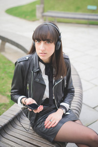 Young beautiful caucasian brown hair woman seated on a bench in a city park listening to the music looking in camera - relax, music concept