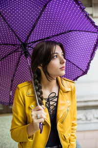 Young beautiful caucasian brown long hair woman outdoor holding umbrella in a rainy day, overlooking pensive - thoughtful, serious, thinking future concept