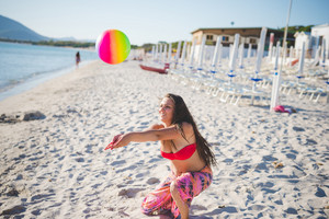 young beautiful caucasian brunette girl at the beach in summertime playing with ball
