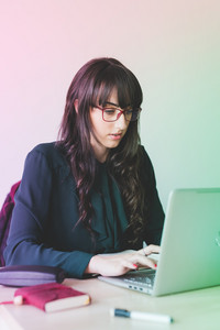 Young beautiful caucasian businesswoman sitting on a desk, using computer - technology, working, business concept