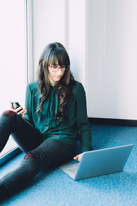 Young beautiful caucasian businesswoman sitting on the floor using computer and smart phone hand hold - multitasking, technology, business concept