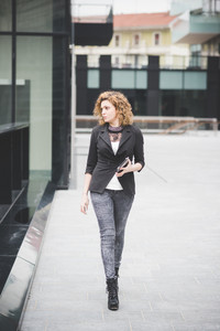 Young beautiful caucasian contemporary businesswoman walking through the city using smartphone and tablet overlooking left - technology, network, business, finance concepts