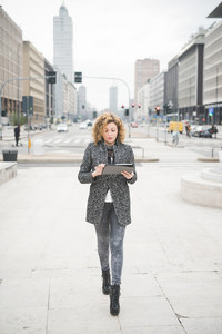 Young beautiful caucasian contemporary businesswoman walking through the streets of the city using a tablet looking the screen - technology, network, business, finance concepts