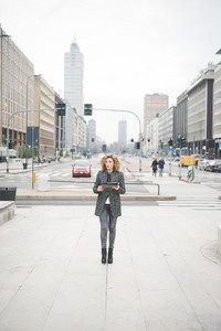Young beautiful caucasian contemporary businesswoman walking through the streets of the city using a tablet overlooking - technology, network, business, finance concepts