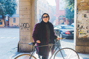 Young beautiful caucasian curvy woman outdoor in the city back light holding bicycle - sportive, green trasport concept