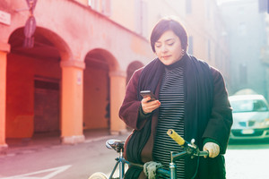 Young beautiful caucasian curvy woman outdoor in the city back light using smart phone holding bicycle - technology, social network, communication concept