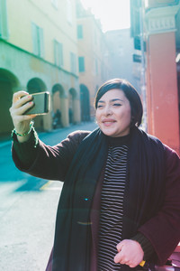 Young beautiful caucasian curvy woman outdoor in the city taking selfie with smart phone hand hold - vanity, social network, technology concept