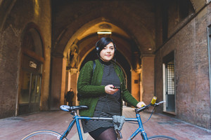 Young beautiful caucasian curvy woman outdoor in the city with bicycle listening music with headphones and smart phone hand hold - music, transport, technology concept