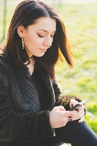 Young beautiful caucasian indie woman with septum piercing outdoor in city back light using smart phone hand hold smiling - social network, technology, happiness concept