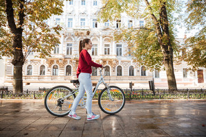 Young beautiful caucasian lady dressed in sweater walking with her bicycle in the city.