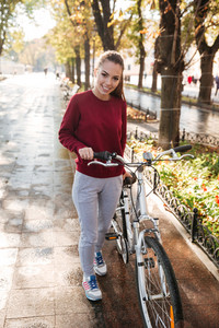 Young beautiful caucasian lady dressed in sweater walking with her bicycle outdoors. Look at camera.