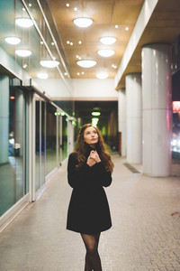 Young beautiful caucasian long brown hair woman outdoor in the city looking over at night - thinking, pensive, serious concept