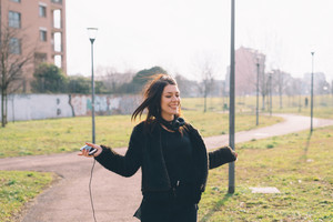 Young beautiful caucasian long brown hair woman with septum piercing feeling free outdoor in the city, holding smart phone - enoying, happiness, freedom concept