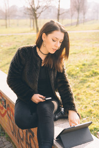 Young beautiful caucasian long brown hair woman with septum piercing using smart phone and tablet outdoor - multitasking, technology, communication concept
