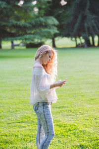 young beautiful caucasian long curly blonde hair woman outdoor in a city park in back light using smart phone handhold - technology, serenity, carefree concept