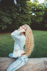 Young beautiful caucasian long wavy blonde hair millennial woman weaving her hair on a braid - hair care, hair style concept