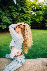 Young beautiful caucasian long wavy blonde hair millennial woman weaving her hair on a braid - hair care, hair style concept