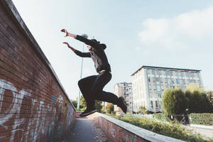 Young beautiful caucasian man doing parkour outdoor in the city in autumn - stunt, acrobat, trick concept
