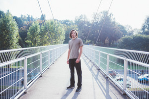 Young beautiful caucasian man standing on a bridge outdoor in back light, looking at camera, smiling - happiness, carefree concept