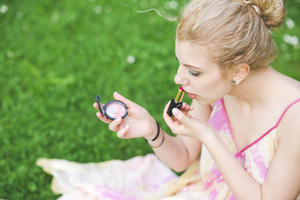 Young beautiful caucasian pale blonde hair woman outdoor putting make up on - vanity, beauty, skin care concept