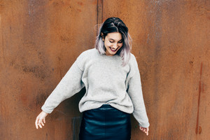 Young beautiful caucasian purple grey hair woman outdoor in the city leaning on colorful wall, eyes closed, smiling - happiness, carefree, serene concept