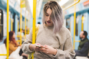 Young beautiful caucasian purple grey hair woman outdoor in the city on the subway using smart phone hand hold - technology, social network, communication concept