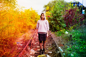 Young beautiful caucasian purple grey hair woman outdoor in the city posing on abandoned railway, looking at camera - serious, pensive, thinking future concept