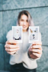 Young beautiful caucasian purple grey hair woman outdoor in the city showing instant photographs - creative, advertising, message concept